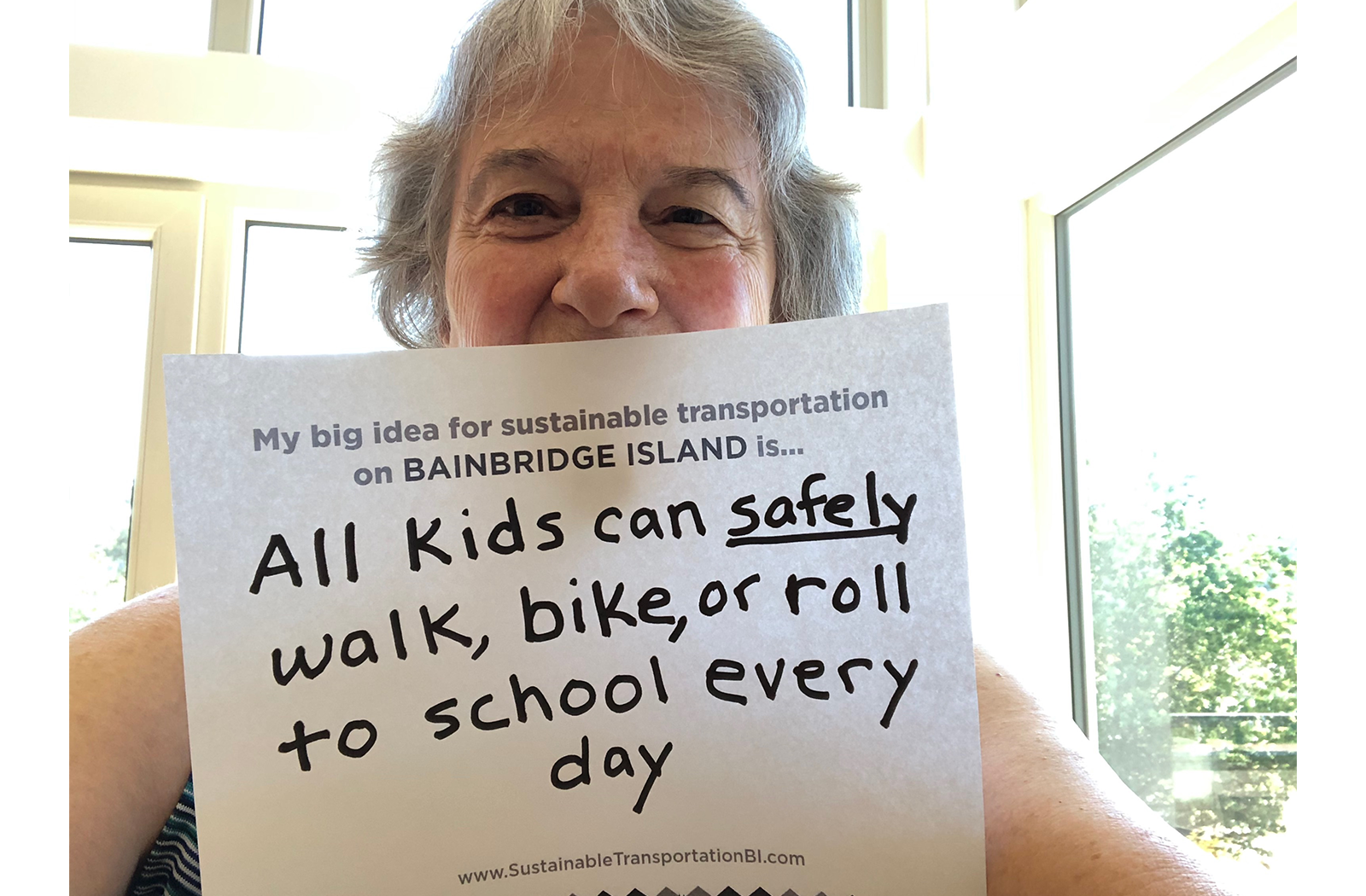 A woman holds a big ideas card that says: All kids can safely walk, bike  or roll to school everyday