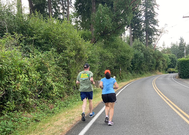 Two people jogging on left side of a two-lane road with vegetation on the shoulder and no sidewalk