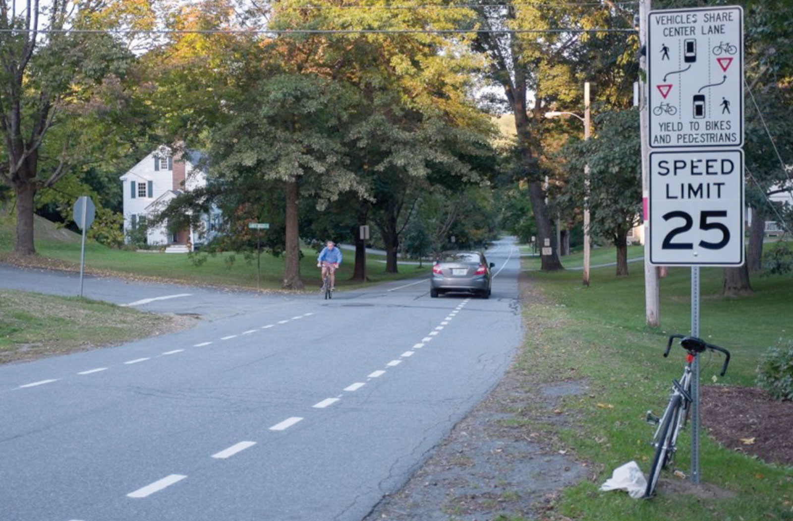 a cyclist passes a car on a road in Massachusetts with a speed limit and road usage sign in the foreground